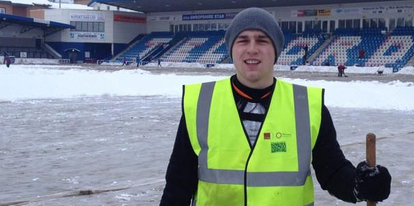 A volunteer with passion and a shovel works to get the game on.