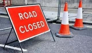 """May be an image of road and text that says """"ROAD CLOSED"""""""